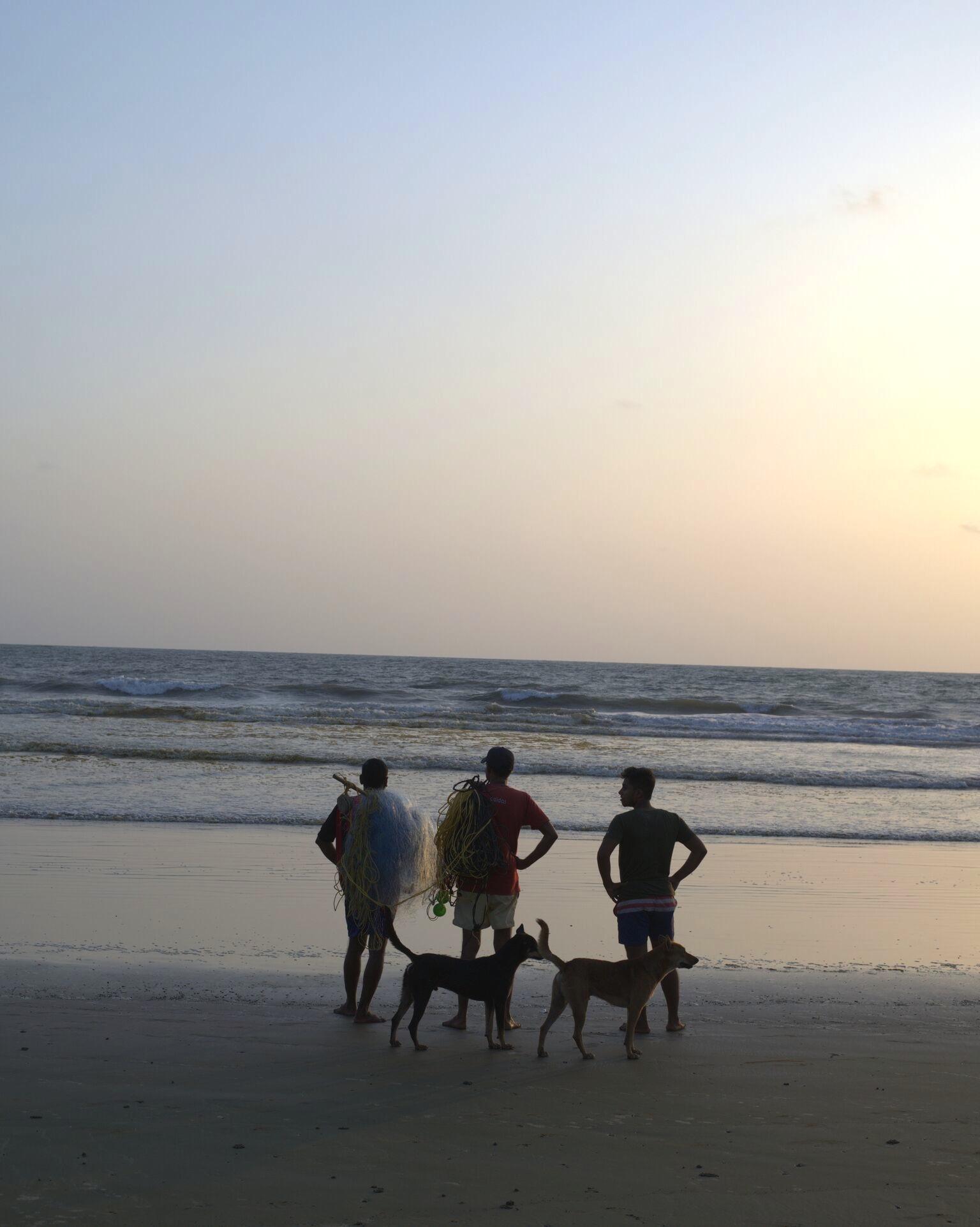 fishermen facing the sea
