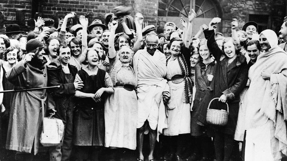 Gandhi greeted by a group of women textile workers